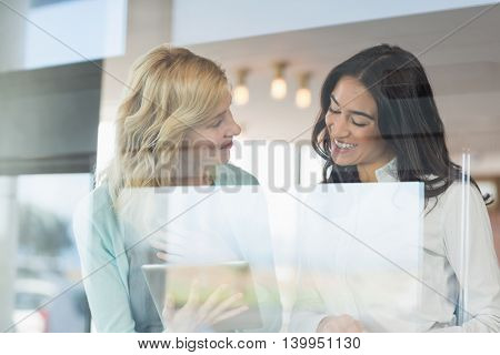 Happy businesswoman using digital tablet at café