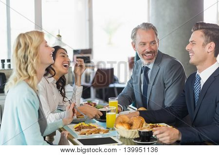 Business people interacting with each other while having meal in restaurant