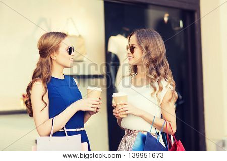 sale, consumerism and people concept - happy young women with shopping bags and coffee paper cups talking at shop window in city