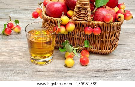 glass of apple juice and ripe apples in a basket. wood background - horizontal photo.