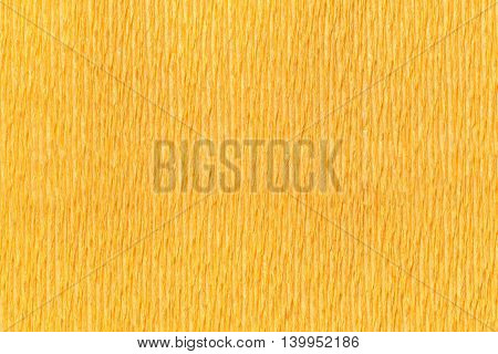 Textural orange background of wavy corrugated paper close-up. Structural crepe yellow cardboard macro shooting.