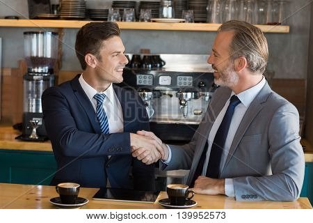 Businessmen shaking hands while having coffee in café