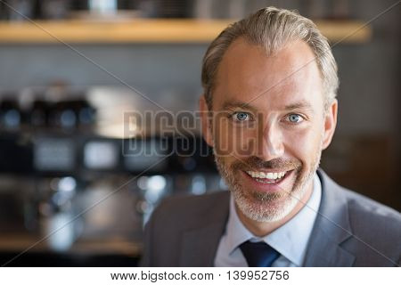 Portrait of happy businessman in café
