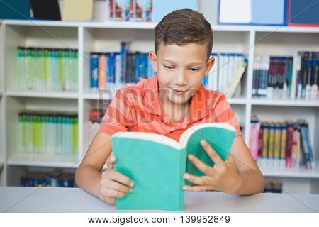 Schoolboy sitting on table and reading book in library at school