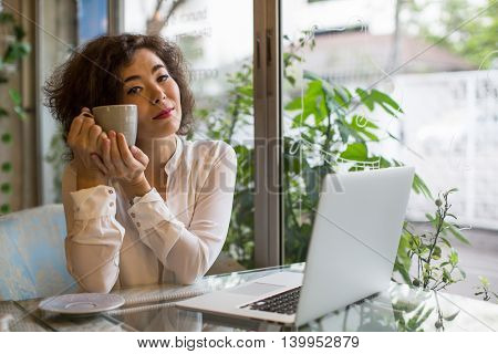 Young asian woman with coffee cup and laptop sitting at a table in a cafe.