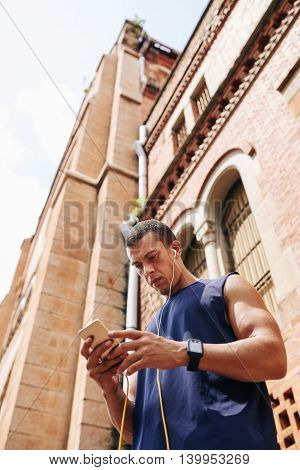 Handsome young sportsman checking his phone before jogging