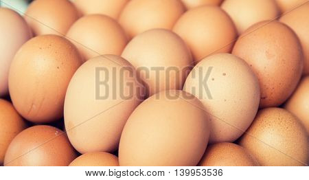 cooking, and food concept - background with many fresh eggs on tray at market