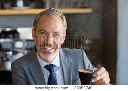Portrait of happy businessman having coffee in café