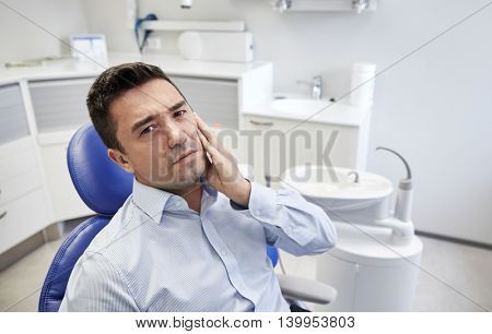 people, medicine, stomatology and health care concept - unhappy male patient having toothache sitting on dental chair at clinic office