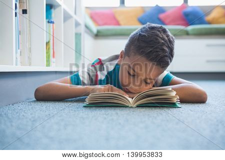 Schoolboy lying on floor and reading a book in library at school