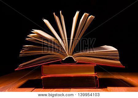 Old book opened in library on wooden shelf. Education background with copy space for text. Shadow dark backdrop.