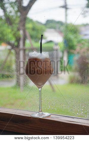 Ice Coffee in long leg glass at windows.