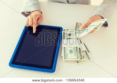 business, finance, saving, technology and people concept - close up of woman hands with tablet pc computer and us dollar money