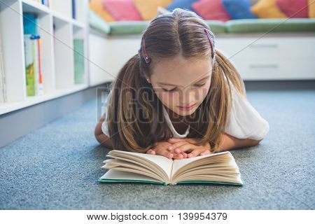 Schoolgirl lying on floor and reading a book in library at school