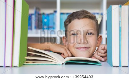 Portrait of schoolboy sitting on table and reading book in library at school