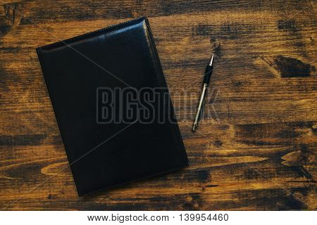 Schedule notepad business agenda with leather covers on office desk top view