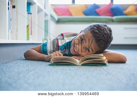 Portrait of schoolboy lying on floor and reading a book in library at school