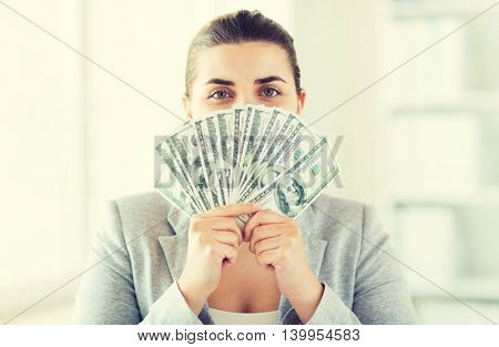 business, finance, saving, banking and people concept - close up of woman hiding her face behind us dollar money fan
