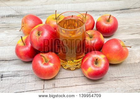 glass of juice and ripe apples on a wooden background. horizontal photo.