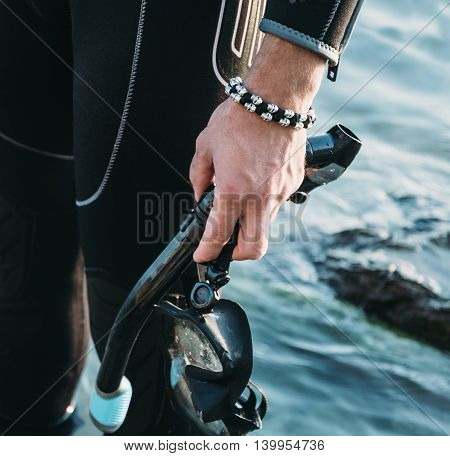 Close-up of diver male hand with snorkel mask on background of sea