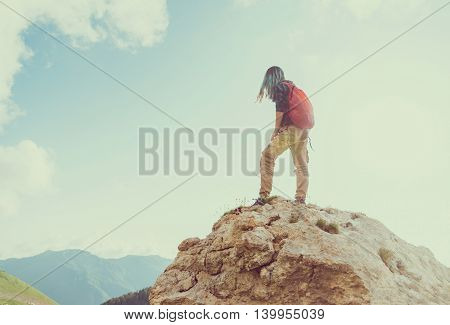 Young woman with backpack standing on rock and looking into the distance instagram color