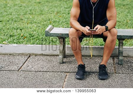 Cropped image of sportsman using application on his phone