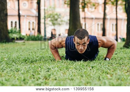 Young sportsman doing push-ups in the park