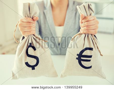 business, finance, saving, banking and people concept - close up of woman hands holding dollar and euro money bags