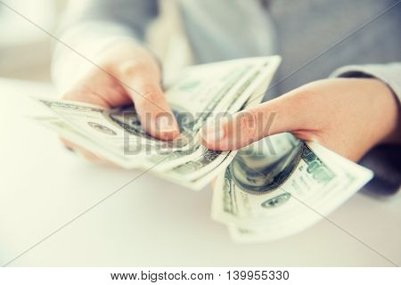 business, finance, saving, banking and people concept - close up of woman hands counting us dollar money