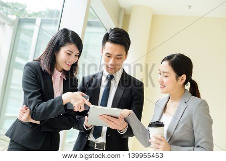 Asian business team talking something on tablet computer