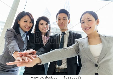 Asian business team joining hands before working