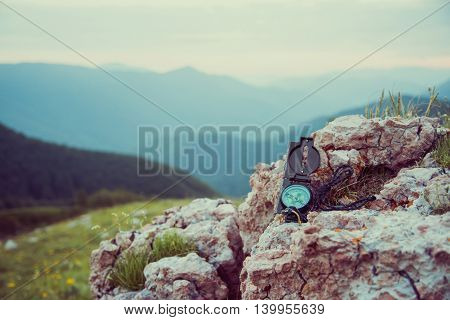 Travel compass on rock stone on background of mountains, outdoor, no people