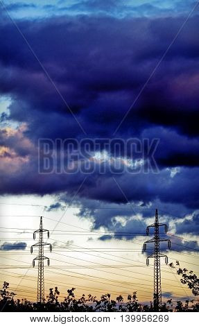 View of electricity pylons against dramatic cloudy sky