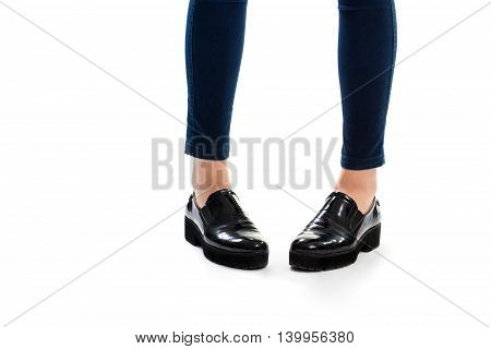 Lady's legs in slip ons. Black glossy footwear. High quality shoes for spring. Durable sole made of rubber.