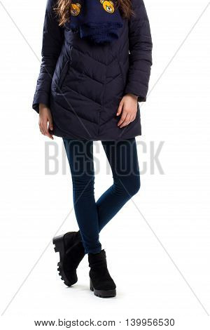 Woman in dark down jacket. Navy pants and black boots. Fashionable winter clothing. Warm footwear from boutique.