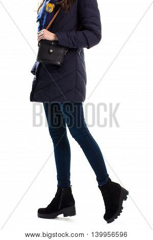 Woman wears dark down jacket. Black ankle boots and handbag. Collection of trendy winter clothes. Waterproof synthetic fabric.