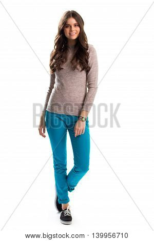 Woman in beige sweater smiling. Turquoise pants and footwear. Nice shoes for spring. Everyday spring outfit.