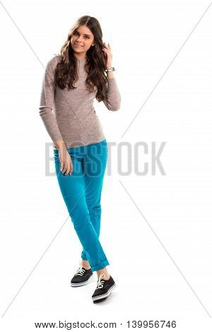 Lady in sweatshirt touches hair. Turquoise pants and beige pullover. Collection of stylish spring clothes. New woolen top.