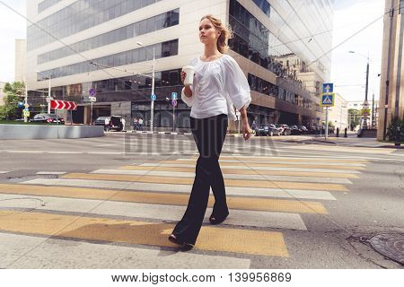 Beautiful blond woman with coffee to go crossing the road. Portrait in motion. Split toned photo