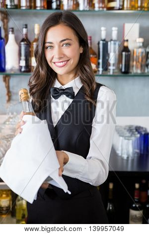 Beautiful waitress holding champagne bottle in restaurant