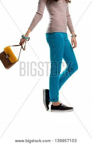 Woman in turquoise pants. Black shoes and beige top. Trendy apparel and footwear. Handbag from spring collection.