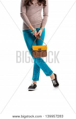 Girl in turquoise pants. Black shoes with white laces. Spring clothes from fashion store. Good set of accessories.
