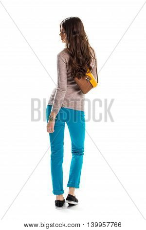 Woman in sweater looking back. Bag and black sneakers. Casual apparel for youth. New strecth pants.