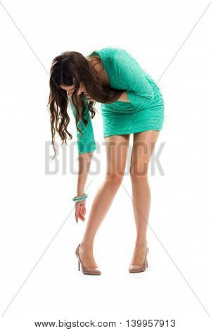 Lady in dress bends down. Short dress and heel shoes. Model wears expensive footwear. She almost sprained her foot.