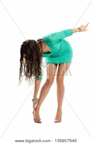 Girl in dress bends down. Short dress of turquoise color. Attractive summer outfit. Legs hurt from new shoes.