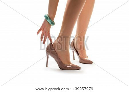 Lady's hand touches heel shoe. Beige heels and turquoise bracelet. New pair of expensive shoes. What to wear on date.