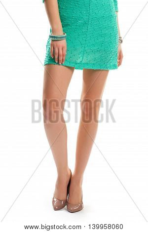 Girl's legs in beige shoes. Short dress and striped bracelet. Model wears glossy heels. Summer night outfit.