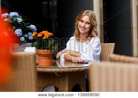 Portrait of cute smiling blond girl sitting in cozy cafe. Split toned photo