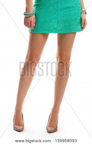 Lady's legs in beige shoes. Short dress of turquoise color. Expensive elegant shoes. Underline beauty and femininity.
