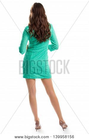 Lady wears turquoise dress. Back view of standing woman. Model in short spring dress. Pair of expensive heel shoes.